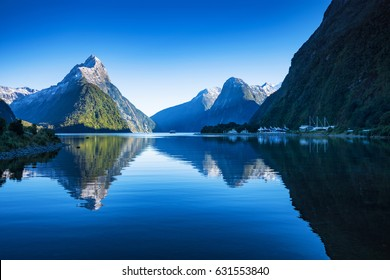 Clear sky in Milford sound, Fjordland national park, south island, New Zealand with a reflection of Mitre peak in the water. - Shutterstock ID 631553840