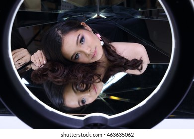 Clear and Smooth Skin Asia Thai Girl with night time make up in studio lighting with mirror reflect herself