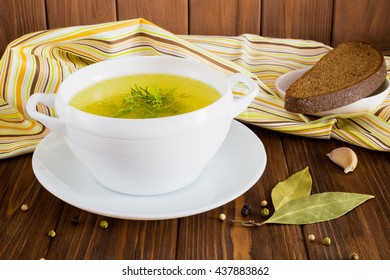 Clear soup with dill and rye bread on a wooden table