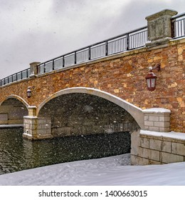 Clear Square Stone arched bridge with lamps over a lake during winter in Daybreak Utah
