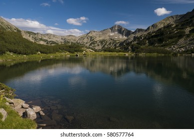 Clear still mountain lake surrounded by rocky apline landscape in Pirin National Park, Bulgaria.