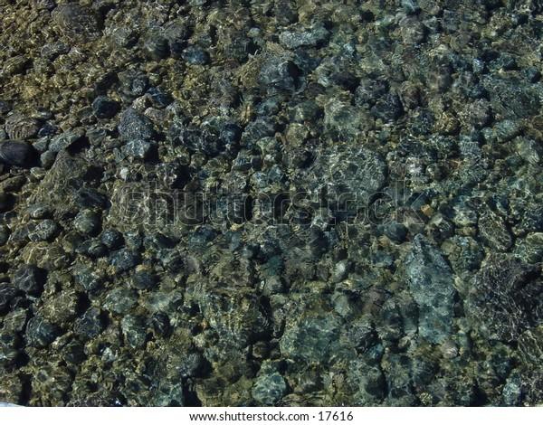 Clear stream in apen colorado, grey river rocks are visible