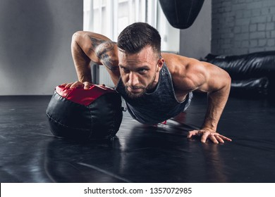 Clear thoughts. The athlete trains hard in the gym, doing exercises with the ball for shoulders, chest, biceps, triceps and forearms, working on his body. Fitness, healthy and self-control concept.