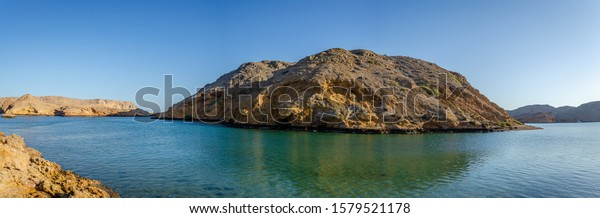 Clear turquoise water, barren hills and clear sky. Oman virgin seascape for you.