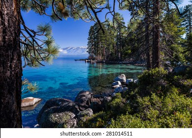Clear, turquoise waters of Lake Tahoe with shoreline of pine forest and mountains