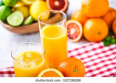 Clear two glasses of fresh pressed orange juice. Orange juice on table with half orange. Multivitamins