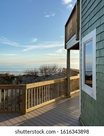 Clear view of dunes and blue sky from beach house deck with reflection in window