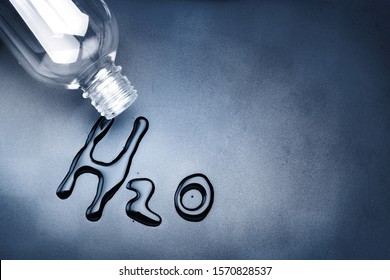 Clear water bottle on dark gray background with H2O symbol letters made from water, Last change of water and Save water before it too late concept,
