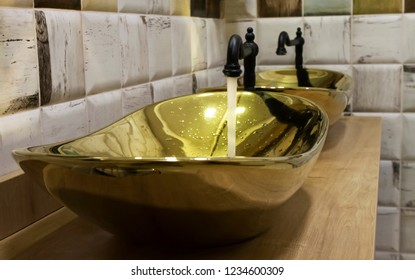 Clear water is flowing from black faucet into the luxury sink made from brass in bathroom|two