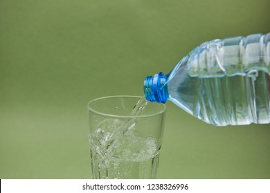clear water flows from a plastic bottle into a glass on green background