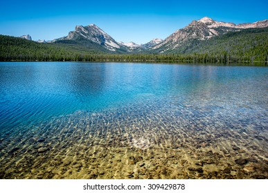 Clear water of an Idaho lake with stones visible beneath a rippled surface in the foreground and forested mountains reflected in the background.