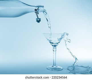 Clear water pour out of bottle splash into glass and spill with a blue back lighting