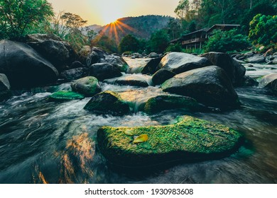 Clear water rapids with green moss grow on the rocks because of the drop in river water levels in the summer.