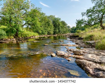 The clear water of the River Ribble flows gently though the Yorkshire Dales near Stainforth