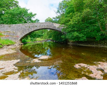 The clear water of the River Ribble passes under an old arched bridge in the Yorkshire Dales near Stainforth.