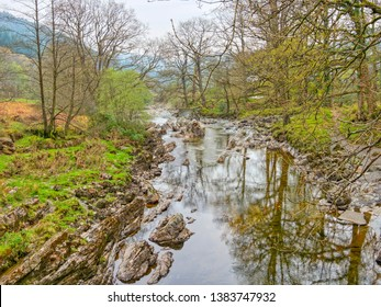 The  clear water of the rock strewn River Mawddach flows between wooded banks on a hazy spring day in Wales