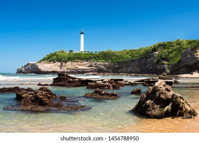 Clear water with rocks on the beach in Biarritz with the lighthouse in the background. Basque country of France.
