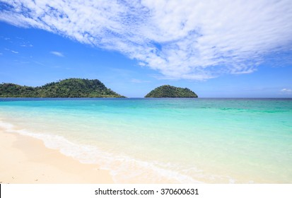 Clear water and sand beach in green sea of tropical island