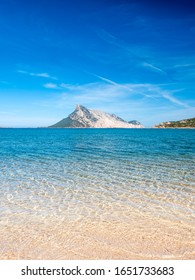 Clear water of sardinian beach called Cala Girgolu, with view on Tavolara island