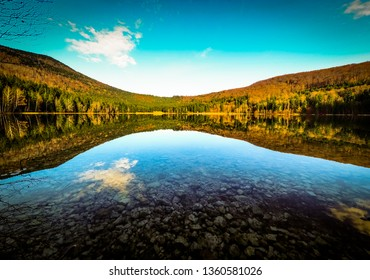 Clear water of the Sf Ana vulcanic lake with the reflections of the skay and the forest in it