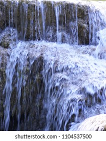 Clear water of a waterfall is tumbling down over brown rocks. A long exposure had made the water look like a flowing sheet of blue-white, with drops of water visible as small white arcs.