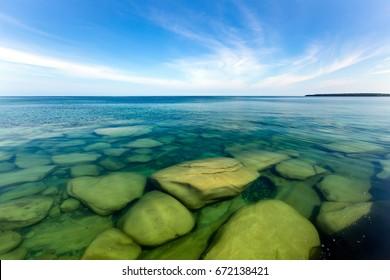 The clear waters of Lake Superior reveal large rocks and stones underwater. This cove, with pristine waters, is located near Au Train Michigan