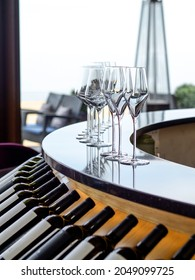 Clear wine glasses on bar counter in wine library with bottles. Bar with large window and sea view. Modern restaurant interior.