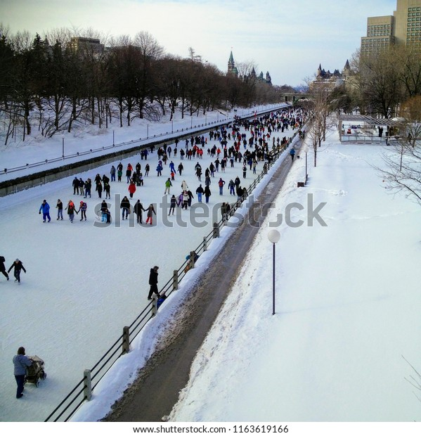 A clear winter's day on a weekend in Ottawa, Ontario, Canada with the city skating along the Rideau Canal