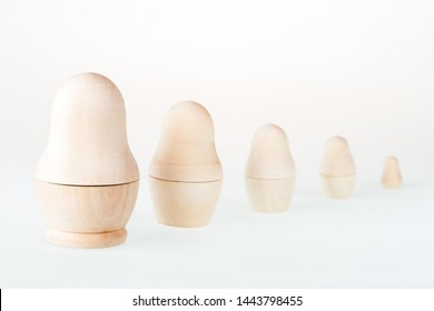 Clear wooden nesting dolls. Russian traditional toy, named matryoshka, on white background. Copy space.