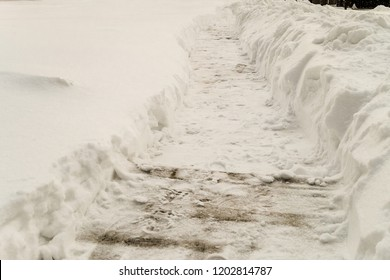 Cleared snowy footpath after heavy snowstorm. Winter background.