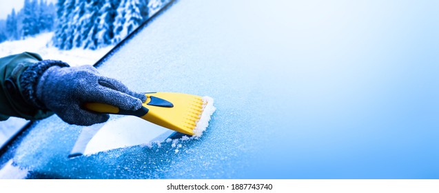 Clearing and remove snow from windshield, Scraping ice. Winter season car window cleaning. Copy space for your text. Panoramatic banner.