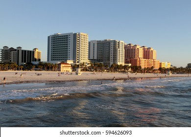 Clearwater, Florida - January 24, 2017: Late afternoon at Clear water Beach viewed from the water looking with people relaxing and colorful buildings reflected on the incoming waves