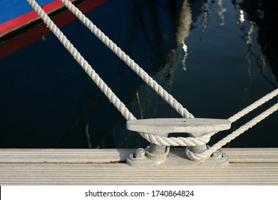 A cleat on a dock and a line tied to a cleat.