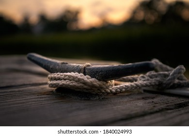 Cleat on a wooden dock during sunset.