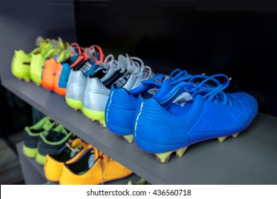 A lot of cleats , soccer boots on shoe rack prepared before football player traning or match competition