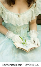 Cleavage of a woman in a beautiful blue dress, she is holding a book open and a flower