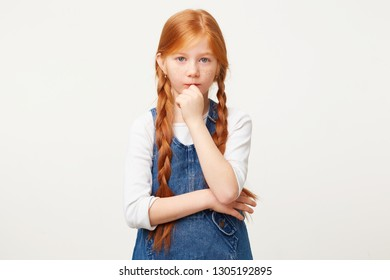 Cleaver smart red-haired child girl with two long plaits thinks, looks with doubt, keeps fist near the chin,white background,in denim overall dress