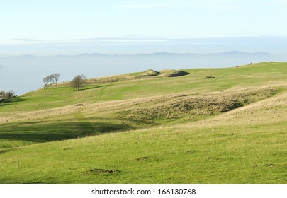 Cleeve Common Hill Fort with The Malvern Hills rising out of the valley fog