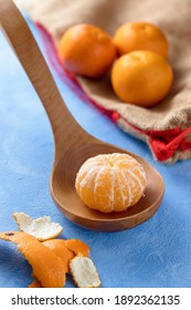 Clementine on wooden laddle on blue surface with burlap bag in background