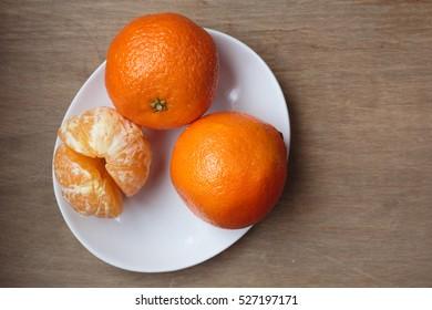 Clementine oranges arranged on a plate.  A hybrid between a mandarin orange and a sweet orange
