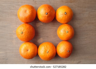 Clementine oranges arranged in a square shape over wooden background.  A hybrid between a mandarin orange and a sweet orange