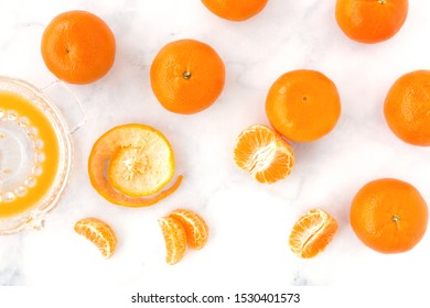 Clementines, clementine segments and juice in a citrus juicer on white marble background. Top view.