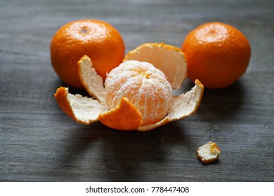 clementines or tangerines or mandarin oranges on rustic wooden table with selective focus