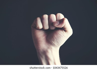 A clenched male fist is up in the air