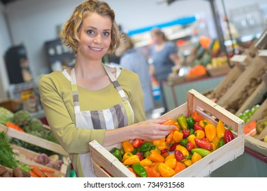 Clerk holding crate of peppers