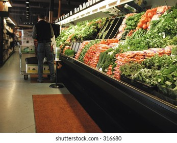 Clerk works in produce section of grocery store.