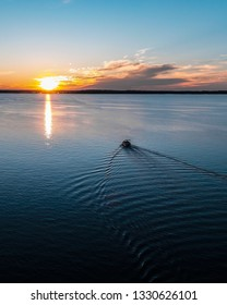 """""""Clermont, FL / USA - 05/02/2018: A pontoon boat gently cruises into the sunset over Lake Minneola."""""""