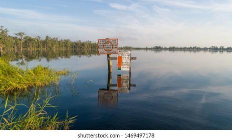 """Clermont, FL / USA - 7-23-2019: Idle Speed No Wake Sign posted in Lake Palatlakaha near the 561 bridge."""