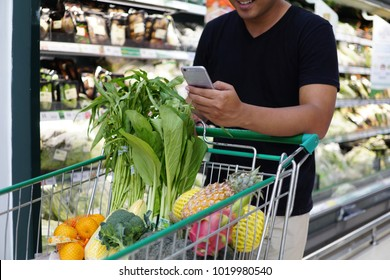 Clese up of a man using smartphone and shopping in a supermarket , shopping concept