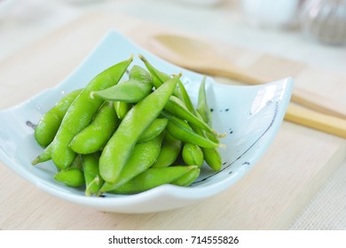 Clese-up edamame, or edamame bean in white square plate on wood bread board.